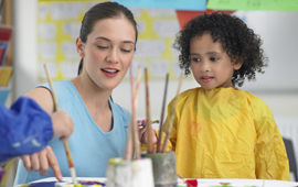 teacher painting with young child